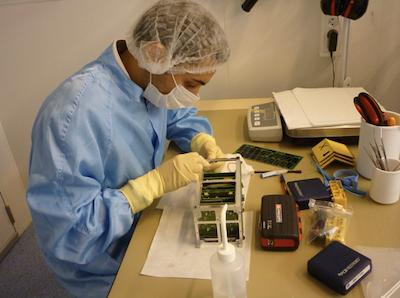 Un étudiant réalisant l'intération et les tests d'X-CubeSat